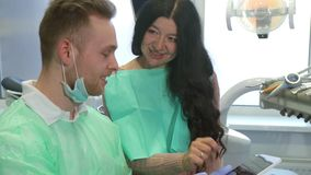 Woman looks at the dentist`s tablet. Senior brunette women looking at the dentist`s tablet. Mature caucasian lady pointing her finger on the screen. Young blond Royalty Free Stock Images