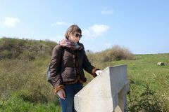 Woman looks at description of sights of Chersonese. In spring stock image