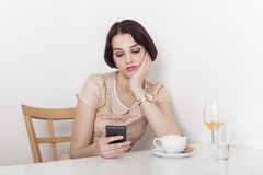 Woman looks disappointed to her mobile phone Stock Photos
