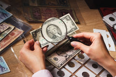 Woman looks at the Dollar bill through a magnifying glass Royalty Free Stock Photo