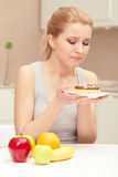 Woman looks at donut and wants to eat it Stock Images