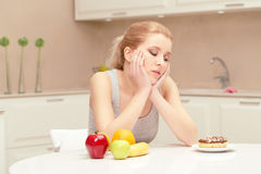 Woman looks at donut and wants to eat it Royalty Free Stock Images