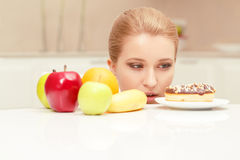 Woman looks at donut and wants to eat it Royalty Free Stock Photo