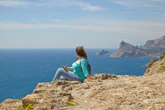 Woman looks at the edge of the cliff on the  sea bay of mountains in the background Stock Image