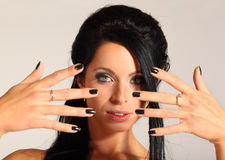 Woman looks through fingers, black manicure Stock Photos
