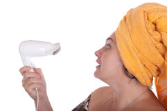 Woman looks at the hair dryer for hair. On a white background Royalty Free Stock Photography