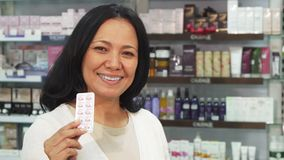 Happy woman showing pills and thumbs up. The woman looks healthy and satisfied. She holds a packet of pills in her hands. Then she shows a thumbs up. A woman is stock video