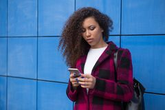 A woman looks at her phone with disgust. With. Clipping path.Young braided hair African American business girl looks into smartphone screen on background with stock photography