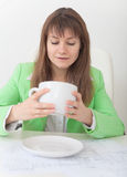 Woman looks in huge cup for coffee Royalty Free Stock Image