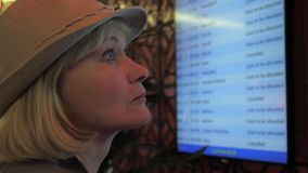 A woman looks at the information board of departures at the airport. Close-up of a traveling woman with a hat on her head. Looks at the information board of stock video footage