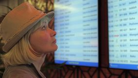 A woman looks at the information board of departures at the airport. Close-up of a traveling woman with a hat on her head. Looks at the information board of stock footage