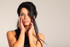 Woman looks inscrutable and touching her face Royalty Free Stock Image