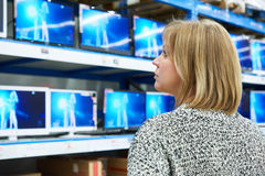 Woman looks at LCD TVs in shop Royalty Free Stock Photos