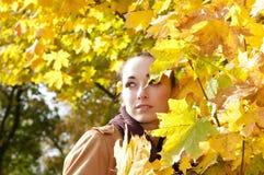 Woman looks through leaves Stock Photo