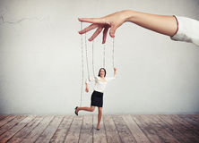 Woman looks like a puppet on strings. A young dark-hear woman in white blouse and black skirt is moving like a puppet while big hand above her is pulling the Royalty Free Stock Image