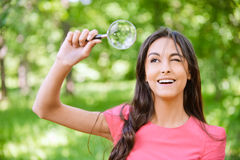 Woman looks through magnifier Stock Images