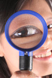 Woman looks through magnifying glass Royalty Free Stock Images
