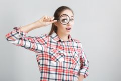 Woman looks through a magnifying glass. Surprised woman in a plaid shirt looks through a magnifying glass Stock Photography