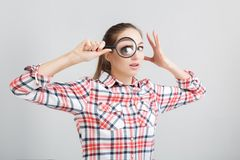 Woman looks through a magnifying glass. Surprised woman in a plaid shirt looks through a magnifying glass Stock Image