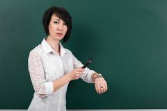 A woman looks through a magnifying glass on watch, a blackboard as a background, a concept of education and business stock images
