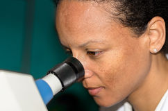 Woman looks through a microscope. Side View of a Young african woman while she is looking through a microscope Royalty Free Stock Images