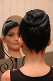 The woman looks into mirror Stock Photography