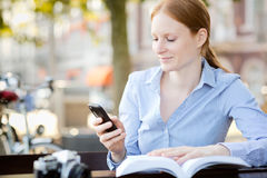 Woman Looks at Mobile Phone in a City Stock Photos