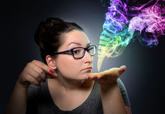 Woman looks at the mystical colored smoke. Royalty Free Stock Photography