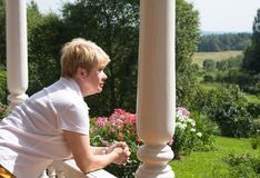 Woman looks at nature from building Stock Photography