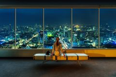 Woman looks at night cityscape Stock Photo