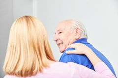 Woman looks after old man in home care stock photos