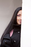 Woman looks out from behind the wall Royalty Free Stock Photos