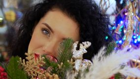 Woman looks out through Christmas baubles. Young curly woman looks out through Christmas baubles, toys and decorations during the Christmas season in winter. The stock video footage