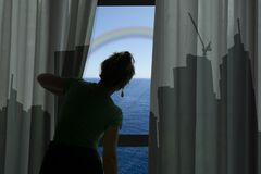 Woman looks out of dark room and sees sea. Concept of wanting to go to the sea