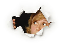 Woman looks out of hole with curiosity Royalty Free Stock Images