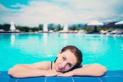 Woman looks out of pool, hanging on the railing. royalty free stock photo