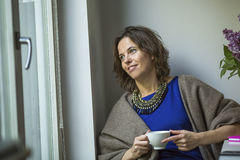 Woman looks out the window holding a Cup of tea. Relax. Royalty Free Stock Photography