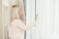 Woman looks out of the window Royalty Free Stock Images