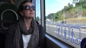 A woman looks out window of public transit in Spain stock video footage