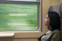 Woman looks out the window of train Stock Photos