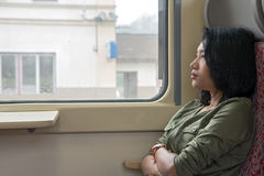 Woman looks out the window of train Stock Images