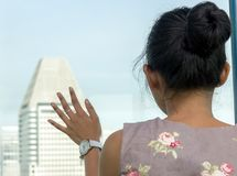 A girl looks out the window at the skyscrapers. Royalty Free Stock Photo