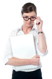 Woman looks over her glasses holding laptop Royalty Free Stock Images