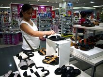 A woman looks at a pair of shoes in the shoe department of SM City mall in Taytay City, Philippines. Royalty Free Stock Image