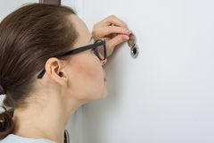 Woman looks through the peephole of the front door in the apartment.  Royalty Free Stock Image