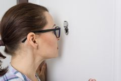 Woman looks through the peephole of the front door in the apartment.  Stock Photography