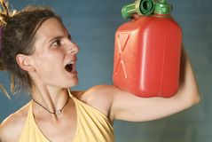 Woman looks at petrol can Royalty Free Stock Image