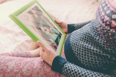 A woman looks at a photo. A pregnant women looks at a photo of a boy. Mom holds a photo frame with a photograph of her son. A small child and memories Royalty Free Stock Photos