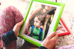 A woman looks at a photo. A women looks at a photo of a boy. Mom holds a photo frame with a photograph of her son. A small child and memories Royalty Free Stock Photos