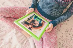 A woman looks at a photo. A women looks at a photo of a boy. Mom holds a photo frame with a photograph of her son. A small child and memories Stock Photography